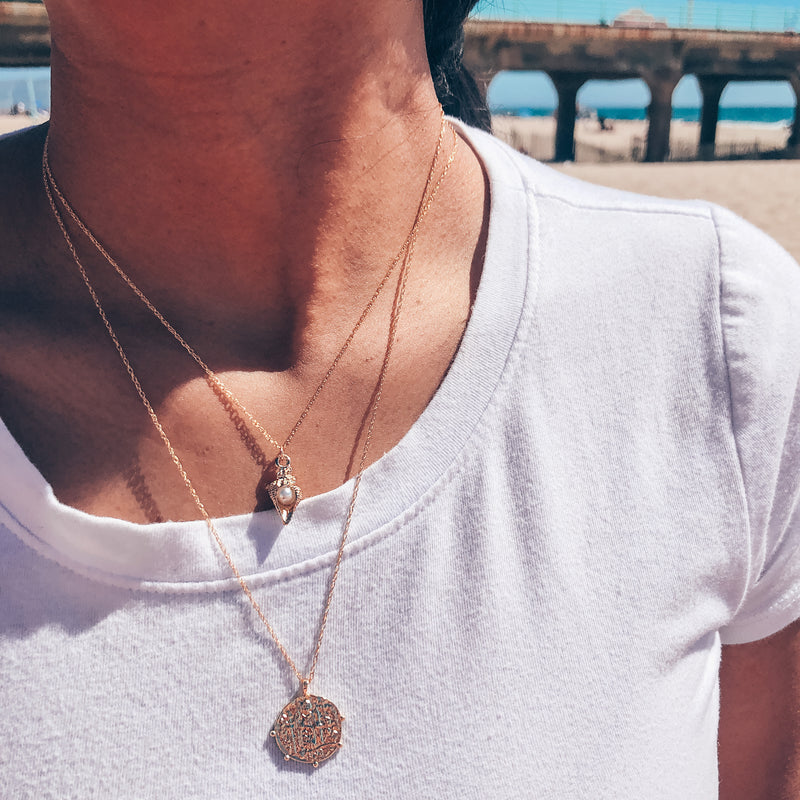 Model photo wearing layered gold necklaces including 14k gold-filled classic pirate coin necklace with scalloped edges