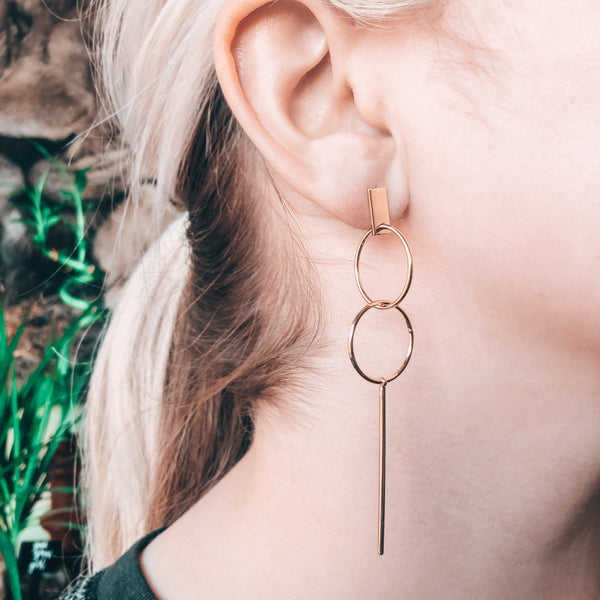 Model photo wearing 14k gold-filled minimal cocktail elegant earrings with a double hoop and stick drop