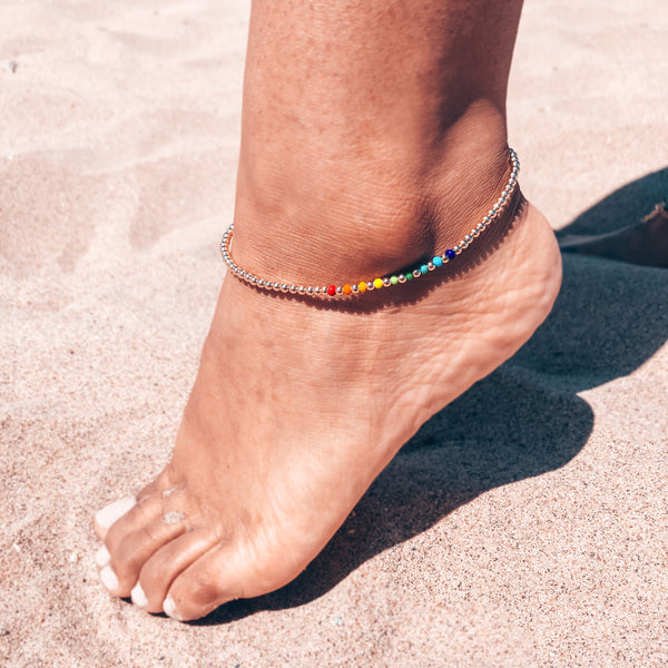 Model photo wearing 14k gold-filled 3mm beaded anklet with rainbow czech glass bead accents with extender