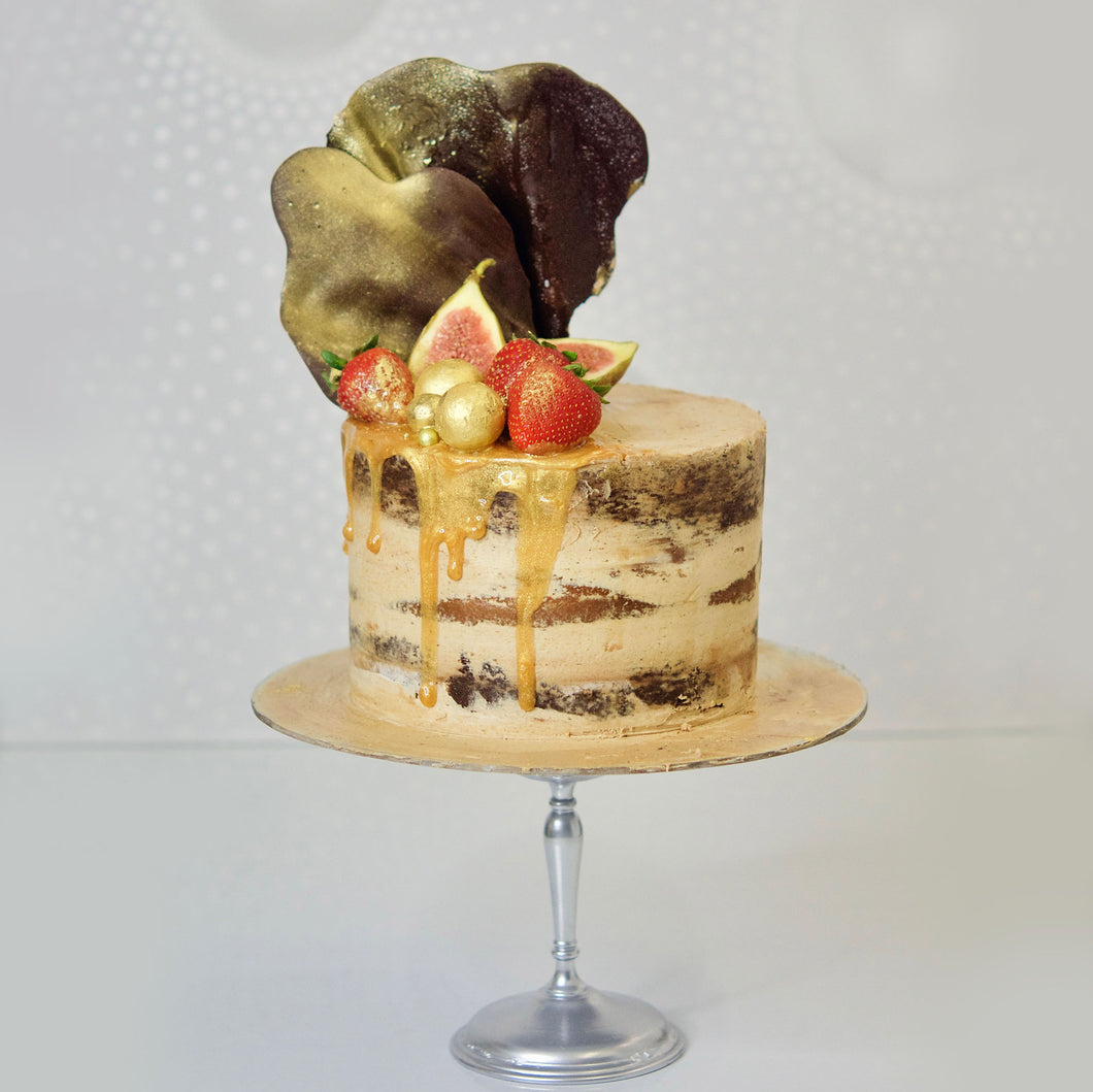 With semi-naked caramel layered cake looks and tastes gorgeous with its buttercream icing, seasonal fruit, chocolate sail and delicious dripping gold.
