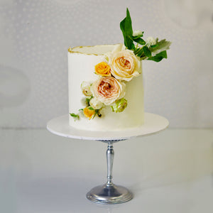 This beautiful birthday or celebration cake has full buttercream icing and gorgeously decorated with stunning fresh blooms / flowers and a touch of gold around the edge.