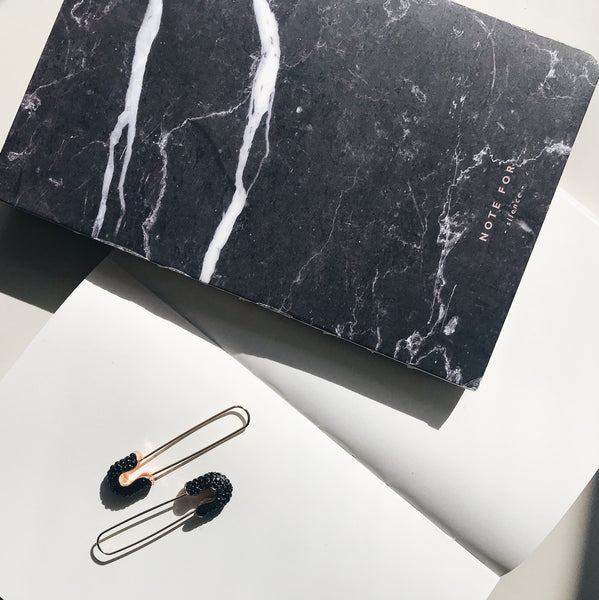 Lifestyle picture of a beautiful, marble printed, black notebook.