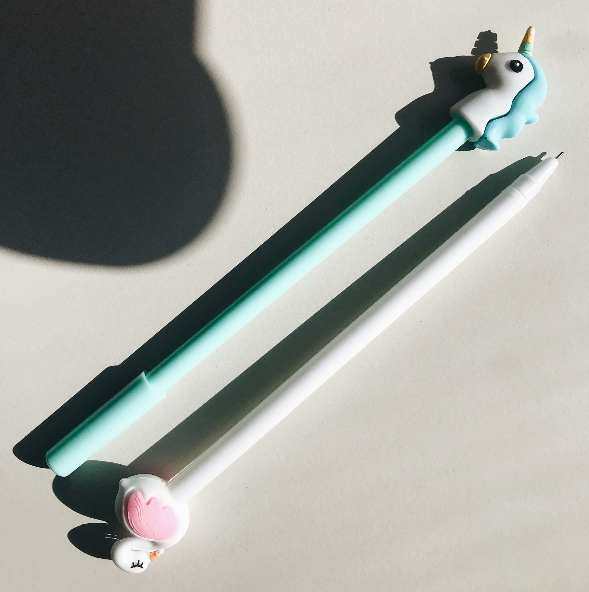 A soft-touch, turquoise unicorn shaped pen with a very fine tip.