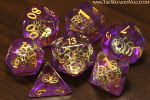 Arcane Sprockets - Dice with tiny golden gears on a purple glittery layer. - The Wizard's Vault