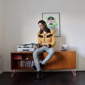 Hipster sits on a vintage sideboard while playing Vinyl LPs on a turntable