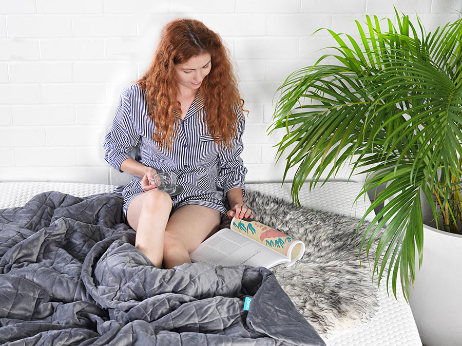 Girl reading magazine with grey weighted blanket