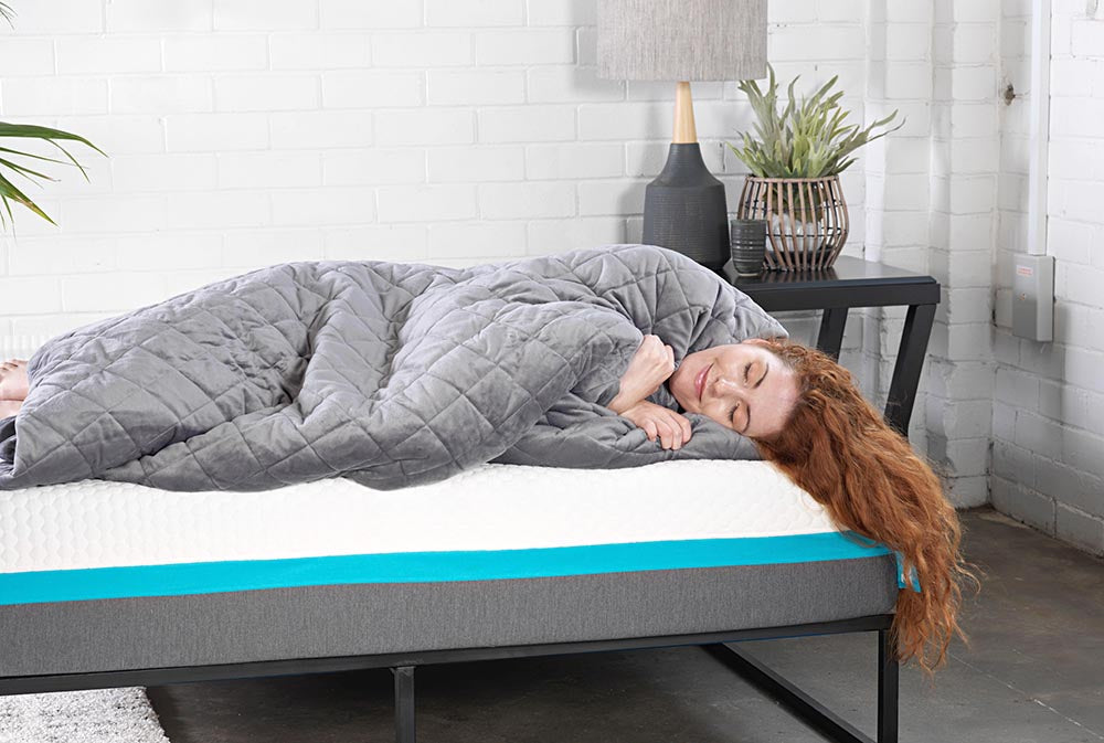 Girl relaxing under grey weighted blanket