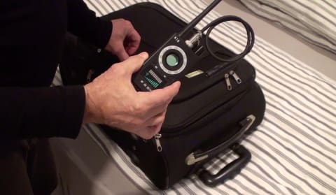 a hand holding a black suitcase
