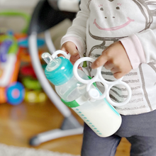 Load image into Gallery viewer, Toddler Drinking Milk With Grasp Toy