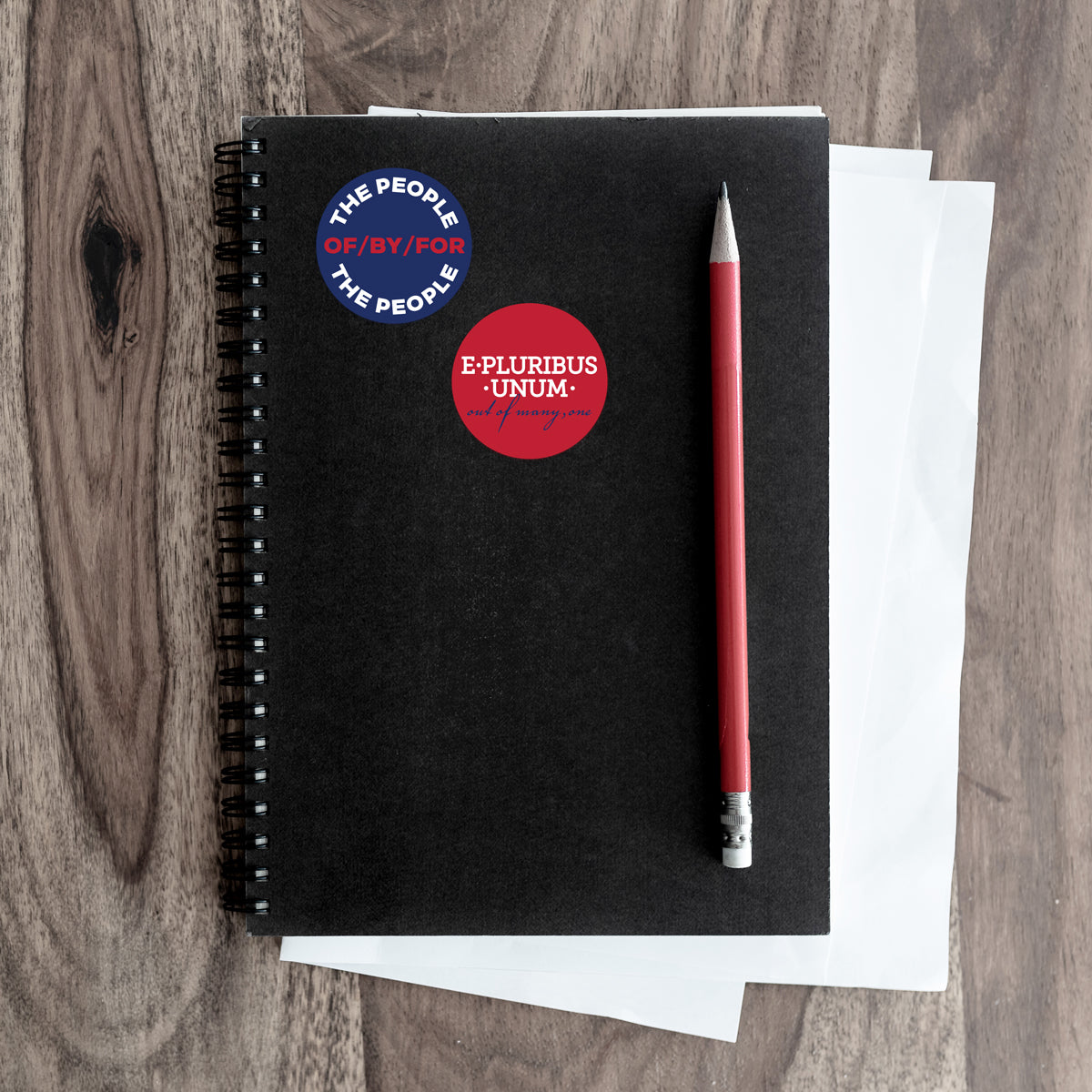 people and e pluribus stickers on a notebook