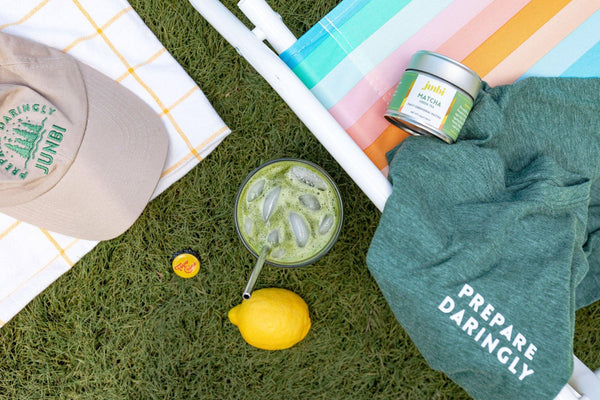 "Junbi hat, matcha tin and a green shirt that says 'Prepare Daringly"" laying on the grass. With a matcha tea and a lemon next to it, representing ""How to Make Sparkling Matcha Lemonade at Home"""
