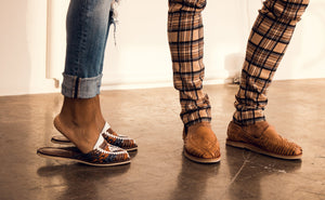 An image of two pairs of legs from the calf down, both wearing leather Mexican huaraches. One pair of legs is a woman, the other pair of legs is a man.