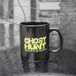 Ghost Hunt Weekends Coffee Cup. Black coffee cup with the green ghost hunt weekends logo silk screen printed on one side.