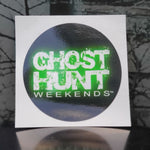 This 3 inch diameter vinyl sticker has a black background with the ghost hunt weekends white logo printed in the middle with a green glow around it.