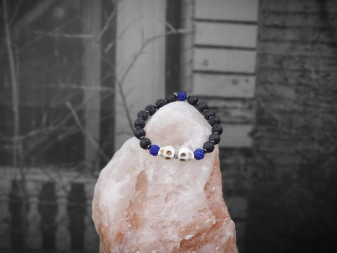 Bone Color Skulls with Blue Sparkles on Lava Stone Bracelet