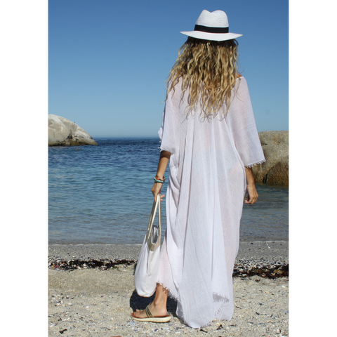 Stylish white summer kaftan styled with hat and handbag