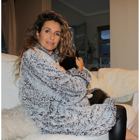 grey and white warm, fluffy winter jacket on couch with cat