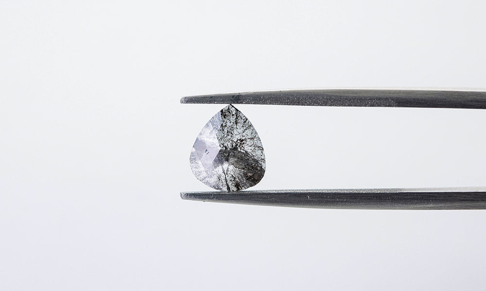 Pear-shaped rose cut salt and pepper diamond in tweezers.