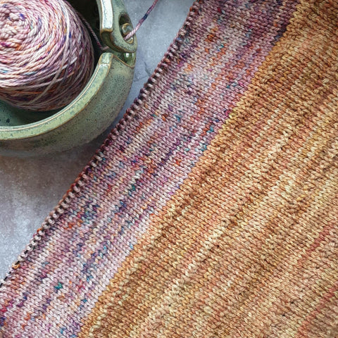 The knitted fabric of a sweater on the needles, lying on the diagonal with a yarn bowl holding a cake of yarn in the corner. The fabric is made up of Gold and Rhino Tears.