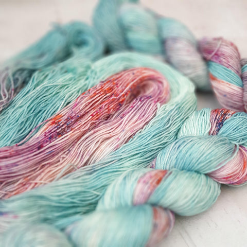 Three skeins of variegated yarn in half pale aqua and half speckled (with blue, purple and orange speckles).