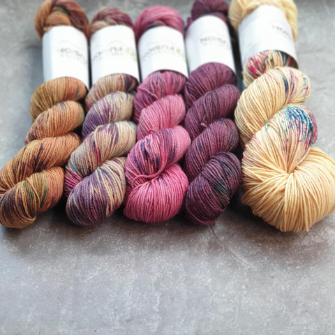 Four 50g skeins lined up next to a 100g skein. The colourways are variegated and from left to right they are Gold, Stone, Raspberry, Tulip and Honey Bloom.