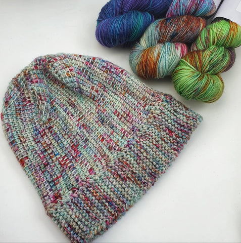 Ishrat Hat laying flat with 3 MCN skeins next to it