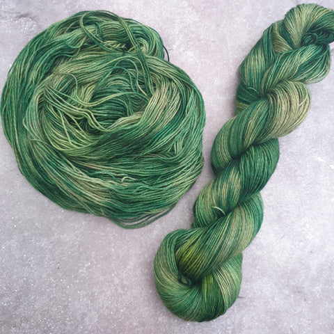 Two green tonal skeins of yarn on a yak blend, one twisted and one spiraling around itself to form a circle.