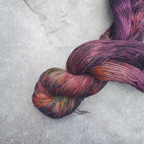 A moody, deep purple skein of yarn half twisted laying diagonally. It has beautiful bright speckles on it.