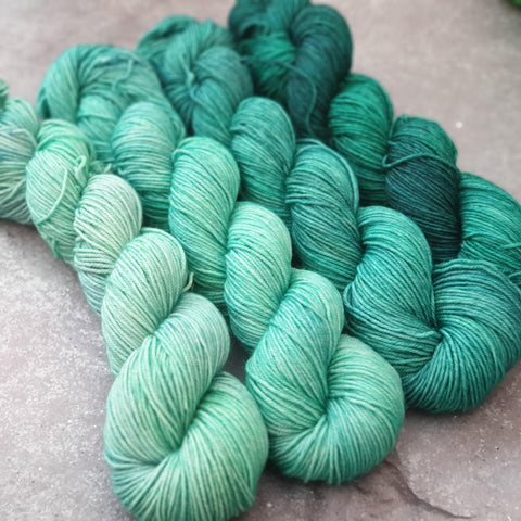 A four-skein fade set going from a light teal shade to a deep, dark teal