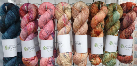 A line of eight vivid but autumnal coloured skeins of yarn, hanging on grid wall hooks