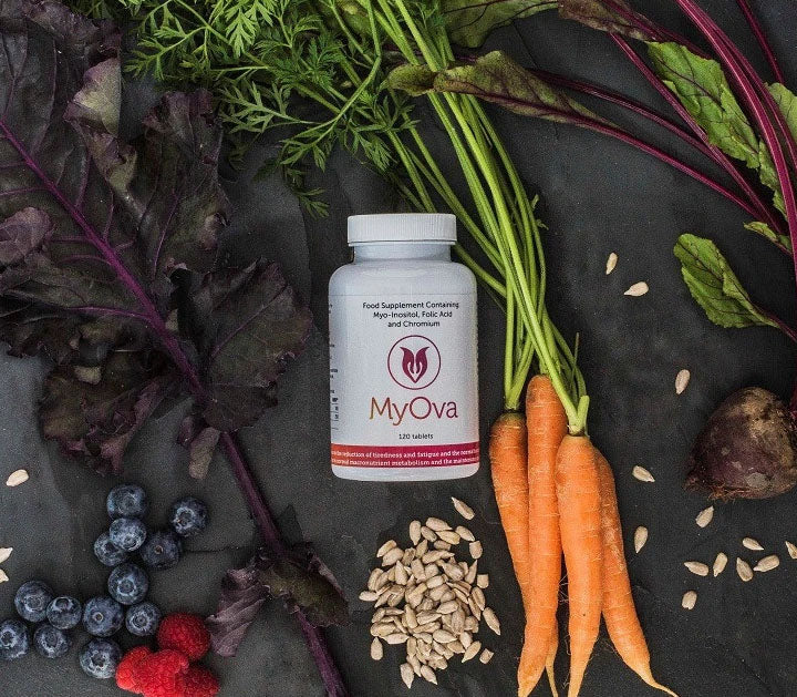 Bottle of MyOva PCOS supplement on a slate with root vegetables and seeds