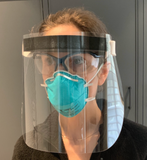 Photo of a woman wearing a protective face shield with goggles and a N95 mask