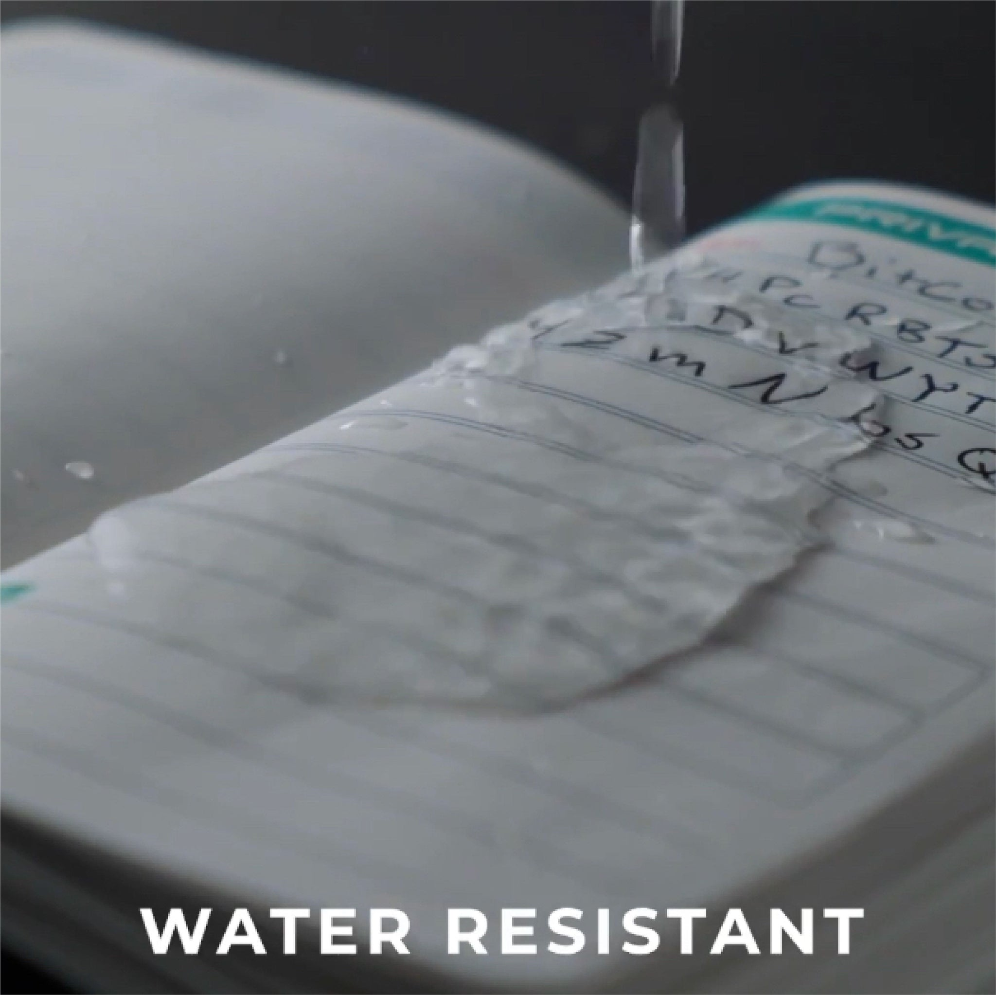 A picture of the Stonebook ™ Notebook having water poured on it, demonstrating it's water resistant pages