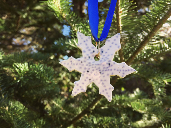 White snowflake ornament with small blue polkadot design. Close up detail image.