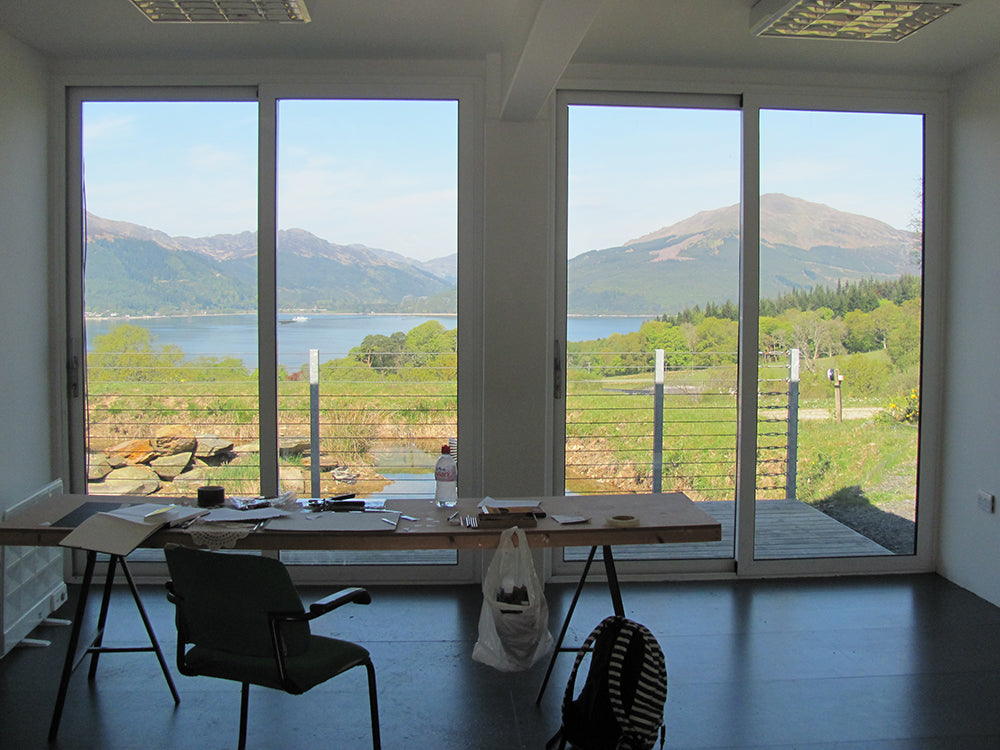 Looking out from the shipping container studio onto hills and the loch