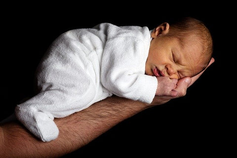 An arm of a man holding a sleeping baby