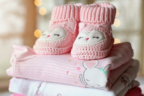 Nicely folded baby clothes, booties on top