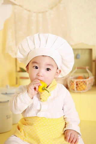 a little boy dressed as a cook, biting into a bright yellow pepper.