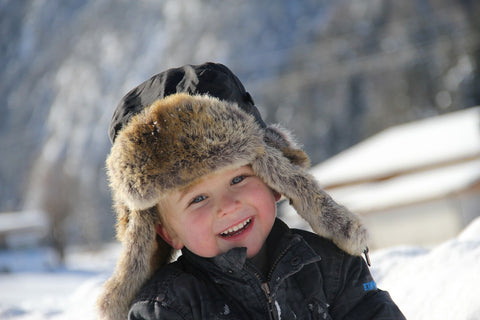A boy wearing fashionable hat with ear flaps