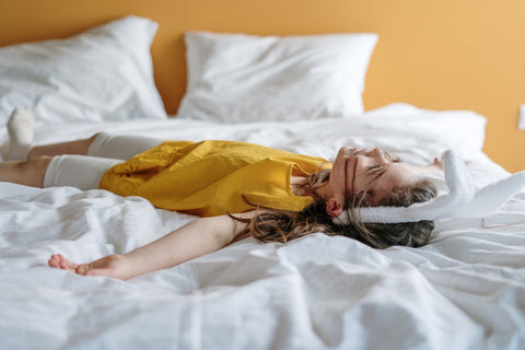 a little girl lying on a bed