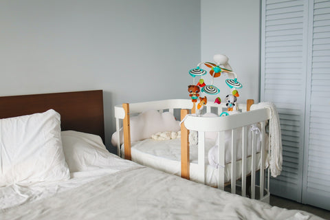 A crib next to a bed