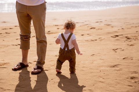 A dad and a baby have having adorable matching outfits for spending a day at the beach