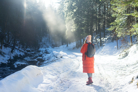 A woman in red jacket walk in the woods during winter