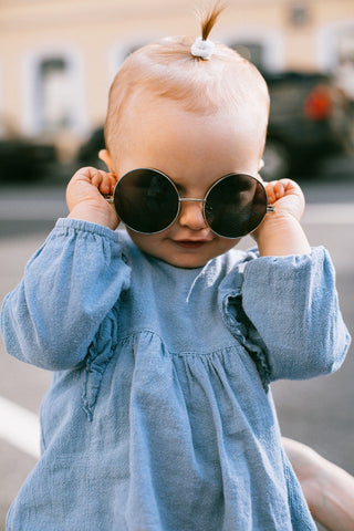 Cute baby girl wearing sunglasses.