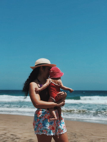 Mom holding a baby on the beach, both wearing light summer clothes and hats.