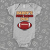"Cool baby onesie saying ""Daddy's first round pick"" and including the image of a football, color grey."