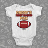 "Cool baby onesie saying ""Daddy's first round pick"" and including the image of a football, color white."