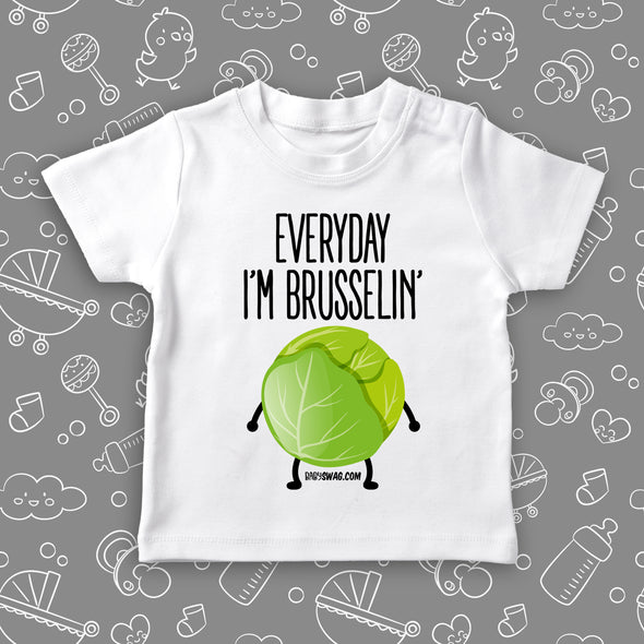 "White todder graphic tee saying ""Everyday I'm Brusselin'"" and a drawing of a Brussel sprout with arms and legs."