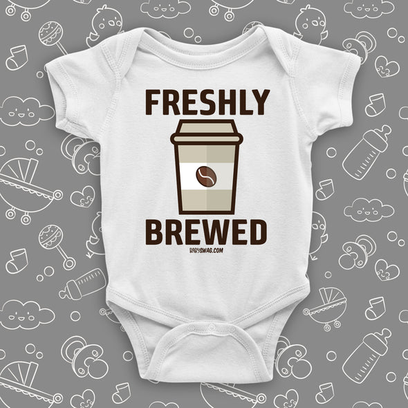 "White cool baby onesie with ""Freshly brewed"" print and an image of a coffee-to-go cup."