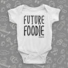 "Unique baby onesie with saying ""Future Foodie"" in white."